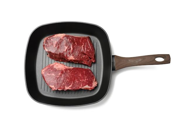 Twee rauwe stukjes rundvlees in een zwarte vierkante grillpan, steaks geïsoleerd op een witte ondergrond, bovenaanzicht