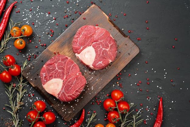 Twee rauwe verse gemarmerd vlees steak op donkere achtergrond, kerstomaatjes en kruiden. detailopname.