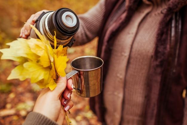 Twee reizigers die thee in de herfstbos hebben
