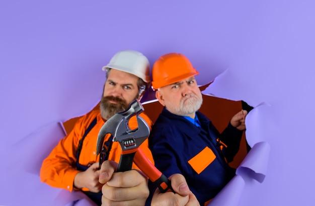 Twee reparateurs die met reparatiehulpmiddelen werken door middel van papieren reclamearbeider in de hamer van de helmreparateur