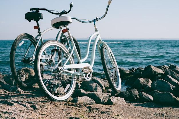 Twee retro fiets op het strand tegen de blauwe zee