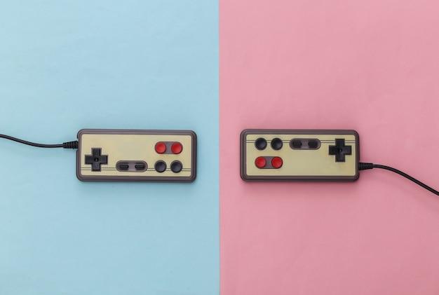 Twee retro gamepads op een blauw-roze achtergrond. pastelkleur trend. gamen, videospelletjes. bovenaanzicht, minimalisme