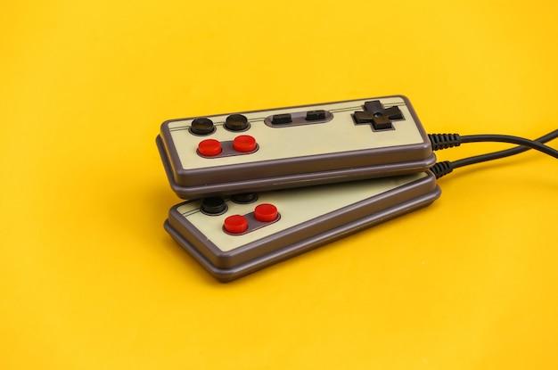 Twee retro gamepads op gele achtergrond. gamen, videospelletjes.