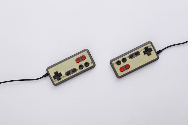 Twee retro gamepads op witte achtergrond. gamen, videospelletjes. bovenaanzicht