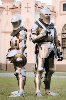 Twee ridders in harnas op de achtergrond van een middeleeuws kasteel. een middeleeuws concept. metalen textuur. Premium Foto