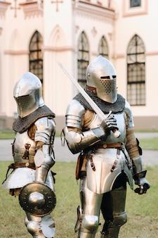 Twee ridders in harnas op de achtergrond van een middeleeuws kasteel. een middeleeuws concept. metalen textuur.