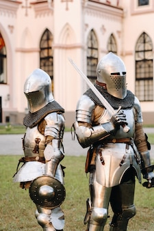 Twee ridders in harnas op de achtergrond van het middeleeuwse kossovsky-kasteel. een middeleeuws concept. metalen textuur.