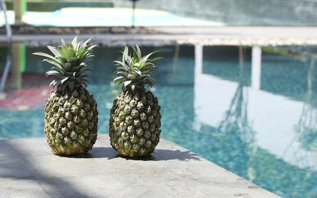 Twee rijpe ananas aan de rand van het zwembad met water. concept zomervakantie in tropische landen. detailopname. kopieer ruimte