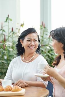 Twee rijpe aziatische dames die van koffie met croissants in koffie genieten