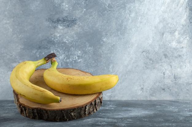 Twee rijpe bananen op een houten bord over grijze achtergrond