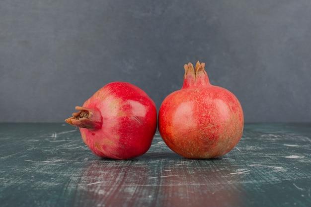Twee rijpe granaatappels op marmeren tafel