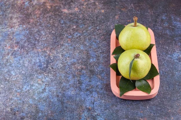 Twee rijpe groene peren met bladeren op een roze houten bord.