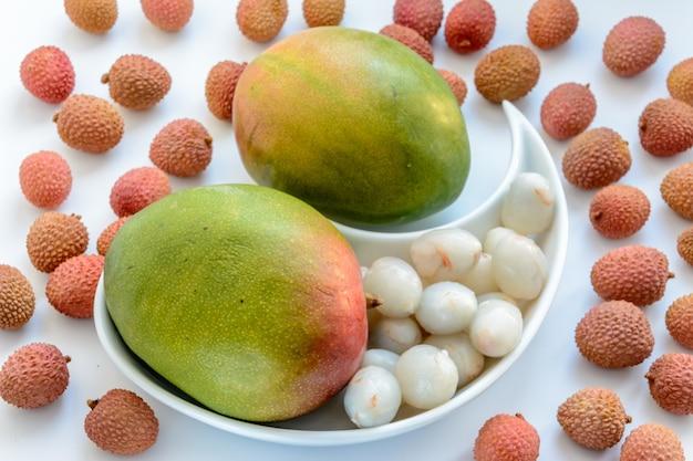 Twee rijpe mango's omgeven door rijpe lycheevruchten op een bord op een witte achtergrond. rijpe lychee zonder schelp.