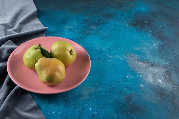 Twee rijpe peer op een bord en stukjes stof, op het blauwe oppervlak