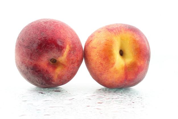 Twee rijpe perziken in de waterdruppels op witte achtergrond. gezond vitaminevoedsel