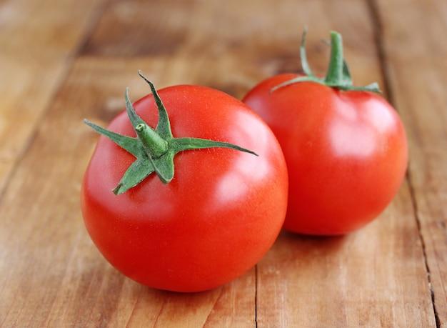 Twee rijpe tomaten op de tafel.