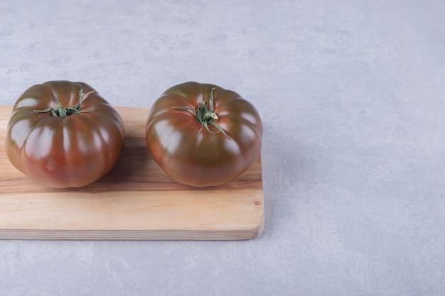 Twee rijpe tomaten op een houten bord.