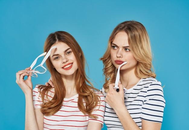 Twee rijpe vrouwen in trendy kleren gestreepte t-shirts bebouwden blauwe achtergrond chatten