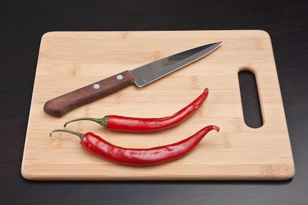 Twee rode chili pepers en mes op de keukentafel