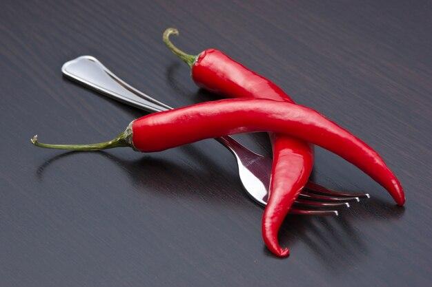 Twee rode chili pepers en vork op de keukentafel