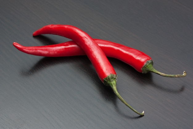 Twee rode chili pepers op de keukentafel