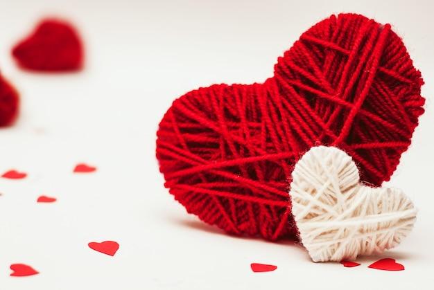 Twee rode en witte clews in vorm van hart gemaakt van garen
