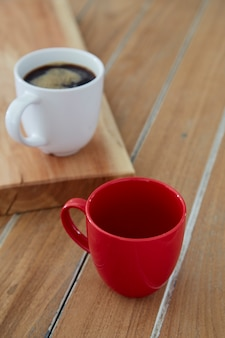 Twee rode en witte mokkoffie op houten