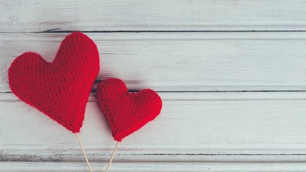 Twee rode gebreide harten op houten achtergrond. het concept van valentijnsdag