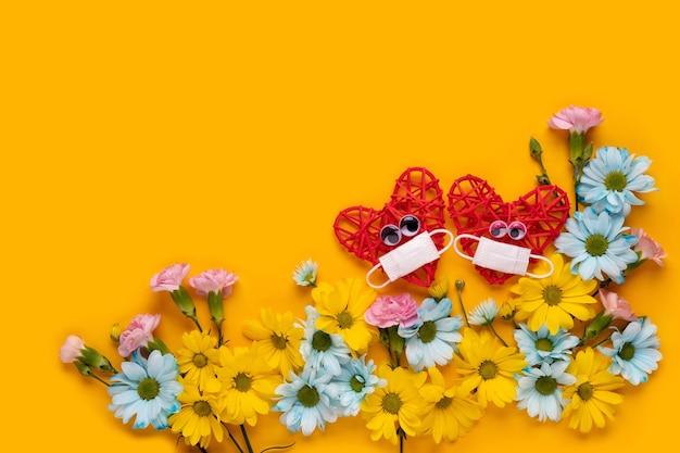 Twee rode harten met een beschermend gezichtsmasker. liefde tijdens het coronavirus. fijne valentijnsdag