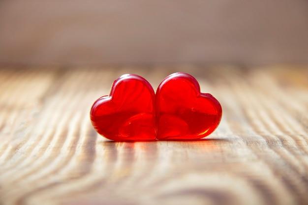 Twee rode harten op houten achtergrond, close-up, valentijnsdag