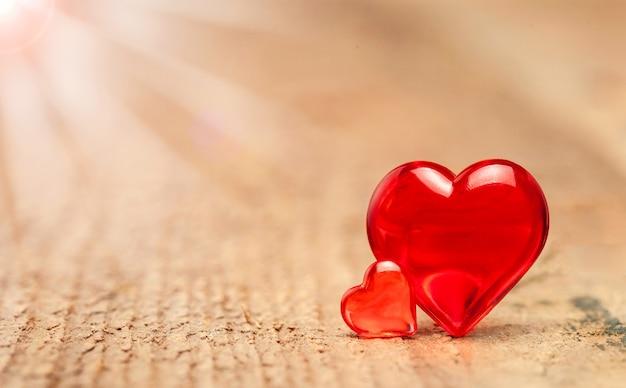 Twee rode harten op houten achtergrond met zonnestralen.