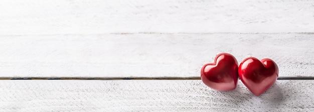 Twee rode harten op houten tafel. romantische panoramatic banner voor valetines of trouwdag.