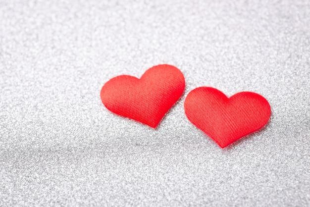 Twee rode harten op zilveren achtergrond