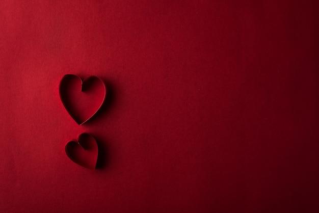Twee rode harten tegen rode achtergrond