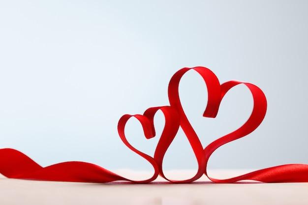 Twee rode harten van lint. valentijnsdag wenskaart, kopie ruimte.