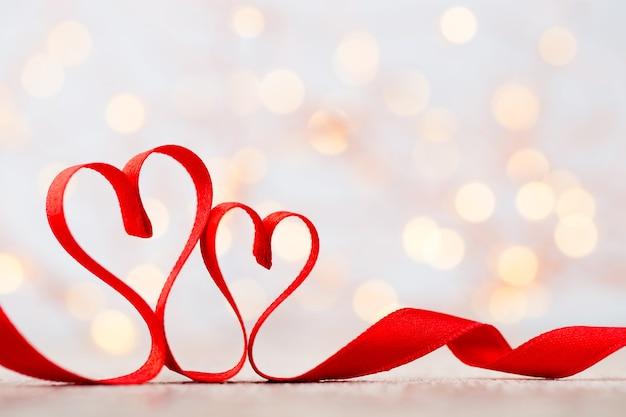 Twee rode harten van lint. valentijnsdag wenskaart.
