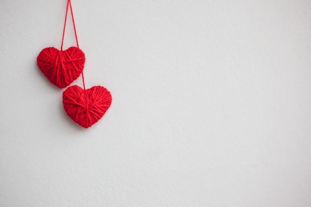 Twee rode harten van wollen draden op een lichte achtergrond. valentijnsdag concept.