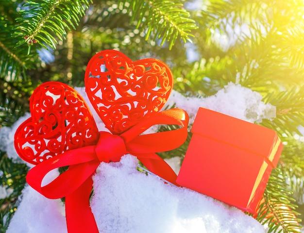 Twee rode harten verbonden met een rood lint en een rode geschenkdoos op de takken van een kerstboom