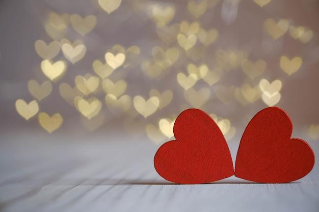 Twee rode houten harten op bokeh achtergrond