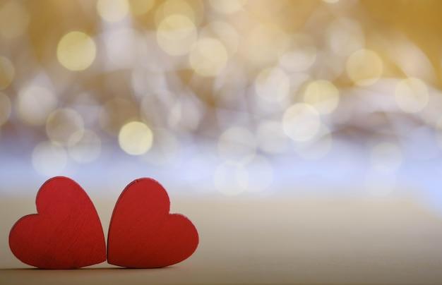 Twee rode houten harten op gouden bokeh achtergrond
