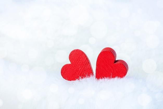 Twee rode houten harten op pluizig glanzend close-up als achtergrond voor st valentine-dag of huwelijk