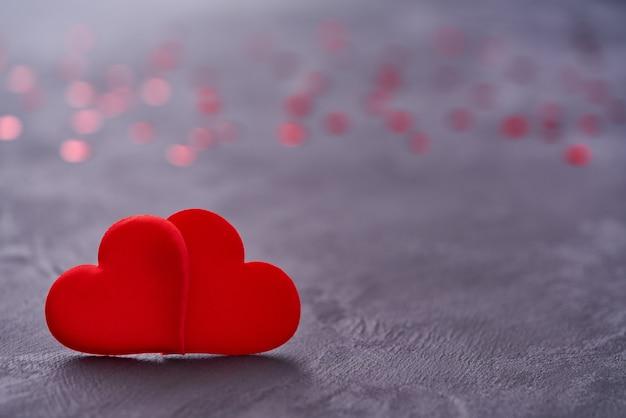 Twee rode liefhebbende harten raken elkaar. valentine achtergrond