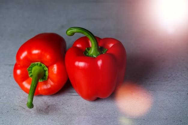 Twee rode paprika's op een grijze tafel