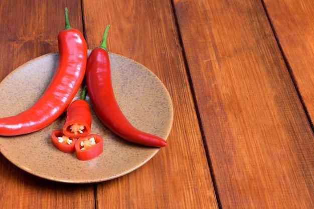Twee rode peulen van chili peper en hun plakjes liggen op een bruine schotel op de achtergrond van houten tafel.