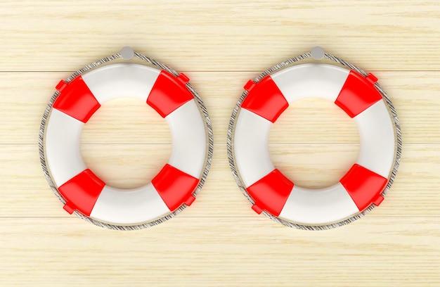 Twee rode reddingsboeien die op een houten muur hangen.