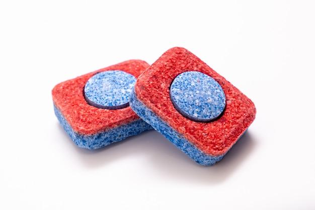 Twee rode tablet van de afwasmachinezeep op witte achtergrond