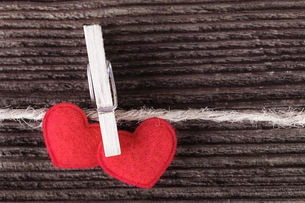 Twee rode textielharten die op een kabel hangen