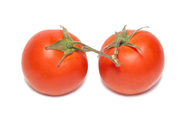 Twee rode tomaten met geïsoleerde waterdalingen