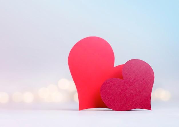 Twee rode valentines in de vorm van harten op een lichte defocusmuur