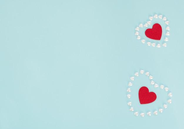 Twee rode vilten harten in harten gemaakt van kleine parelharten op blauwe achtergrond. valentijnsdag, bruiloft, liefde, geluk concept.